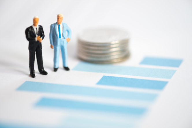 Two toy business men looking over graph, standing next to stack of quarters.