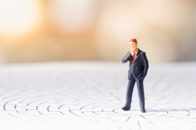 Toy business man standing on a maze.